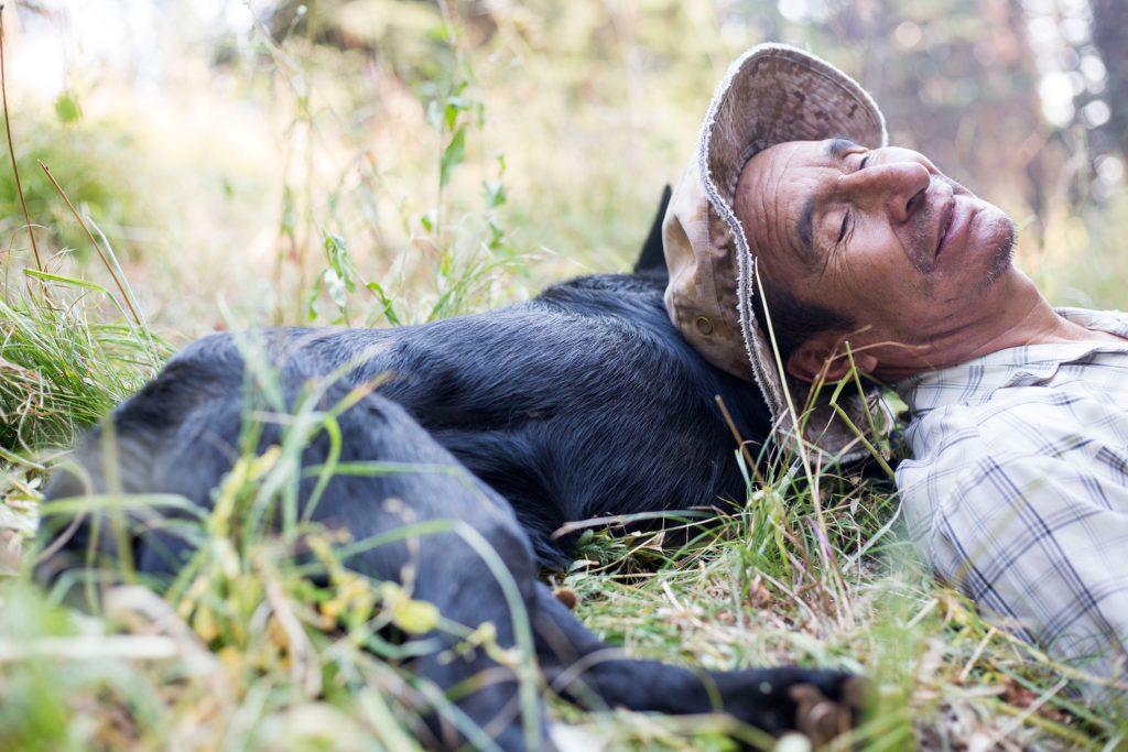 Image: Heraclio DeLaCruz takes a break with his herding dog, Oso, in the Okanogen-Wenatchee National Forest near Cle Elum, Wash. Herders walk dozens of miles per week moving their sheep. (© Copyright Sofia Jaramillo)